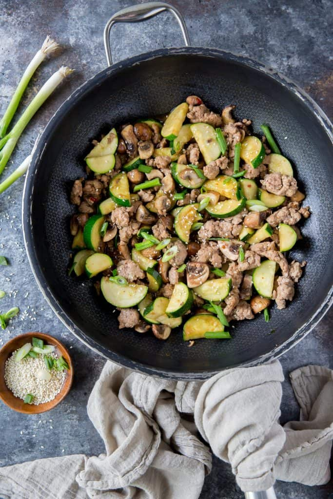The ground pork stir fry in a large skillet shot from over the top.