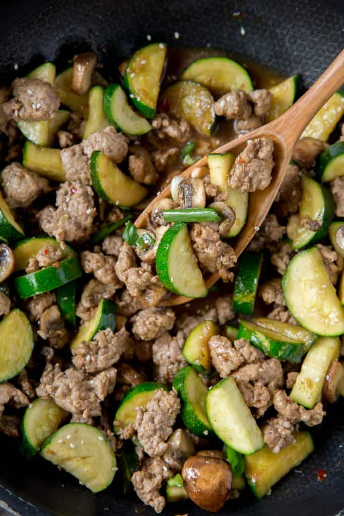 A close up of the ground pork, zucchini, and mushrooms.