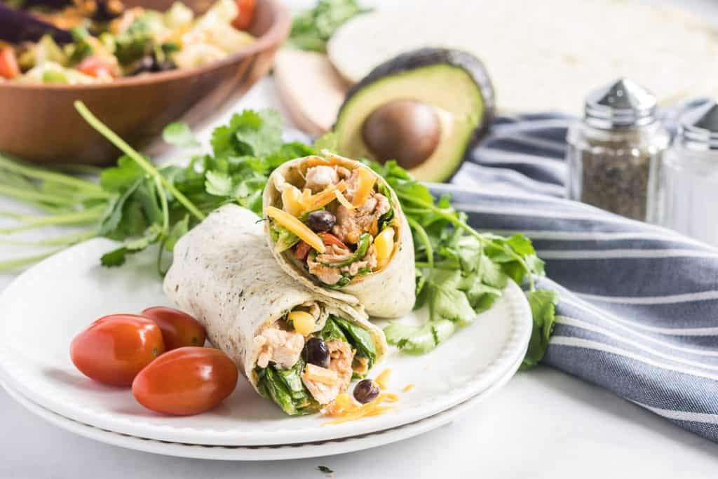 A BBQ Chicken Salad Wrap cut in half and stacked on a white plate with grape tomatoes and cilantro.