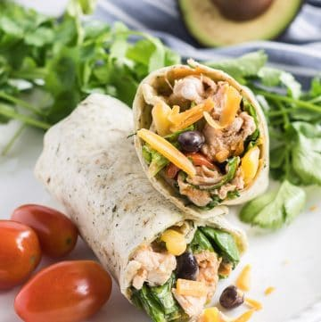 Two BBQ Chicken Salad Wraps on a white plate with grape tomatoes and cilantro.