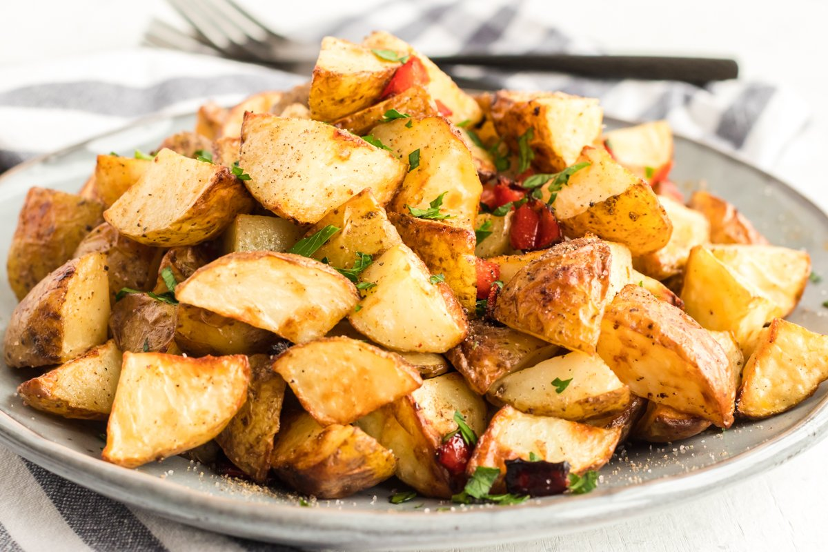 A plate filled with chunks of air fried potatoes and diced red bell pepper.