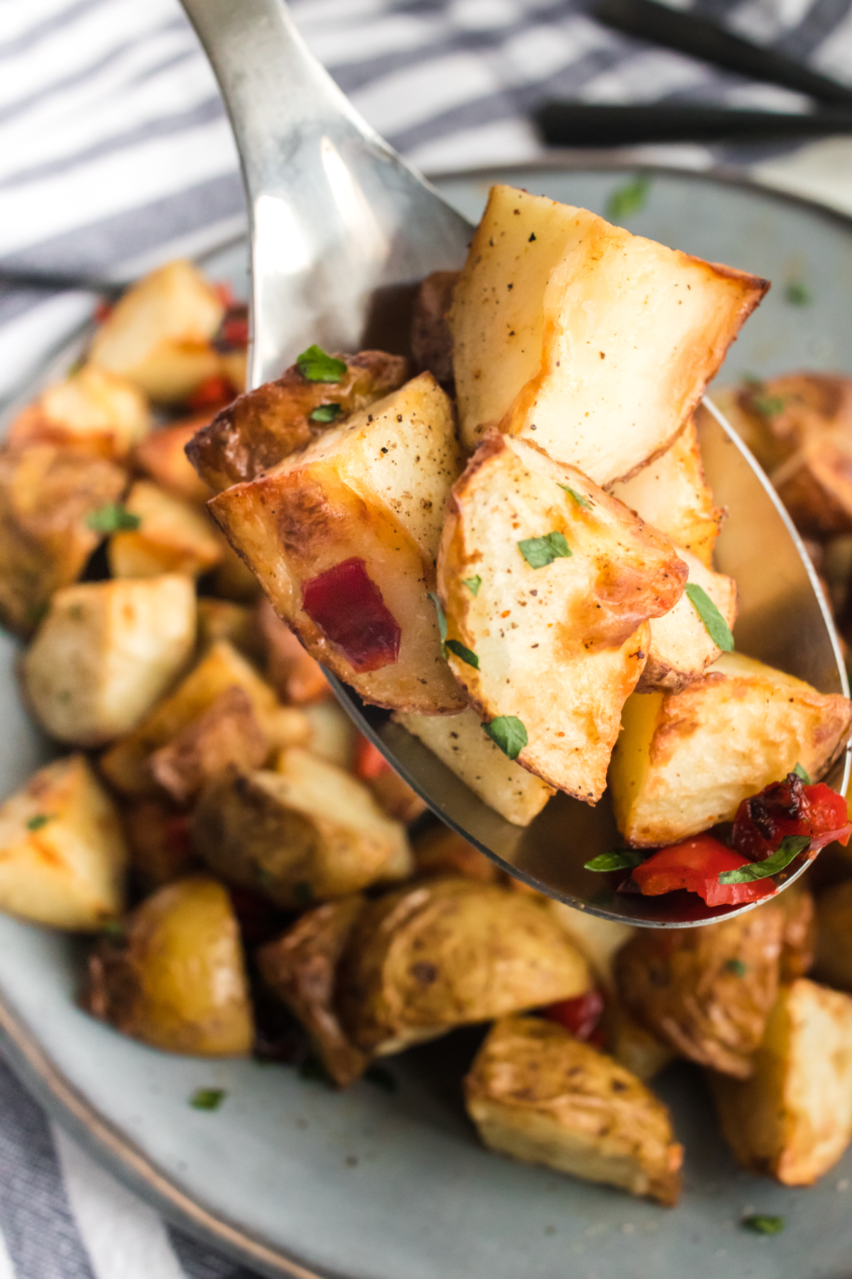 A spoon lifts up some chunks of cooked potatoes with red bell peppers.