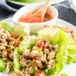 Chicken Lettuce Wraps on a white plate with a bowl of sweet chili sauce.