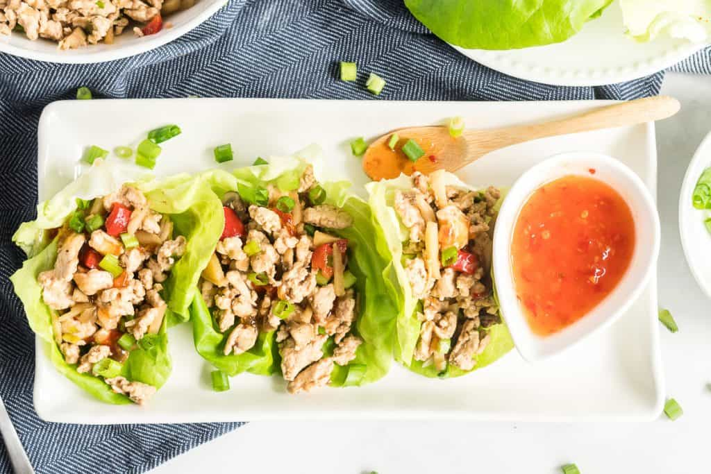 Three Chicken Lettuce Wraps on a white tray with sweet chili sauce.