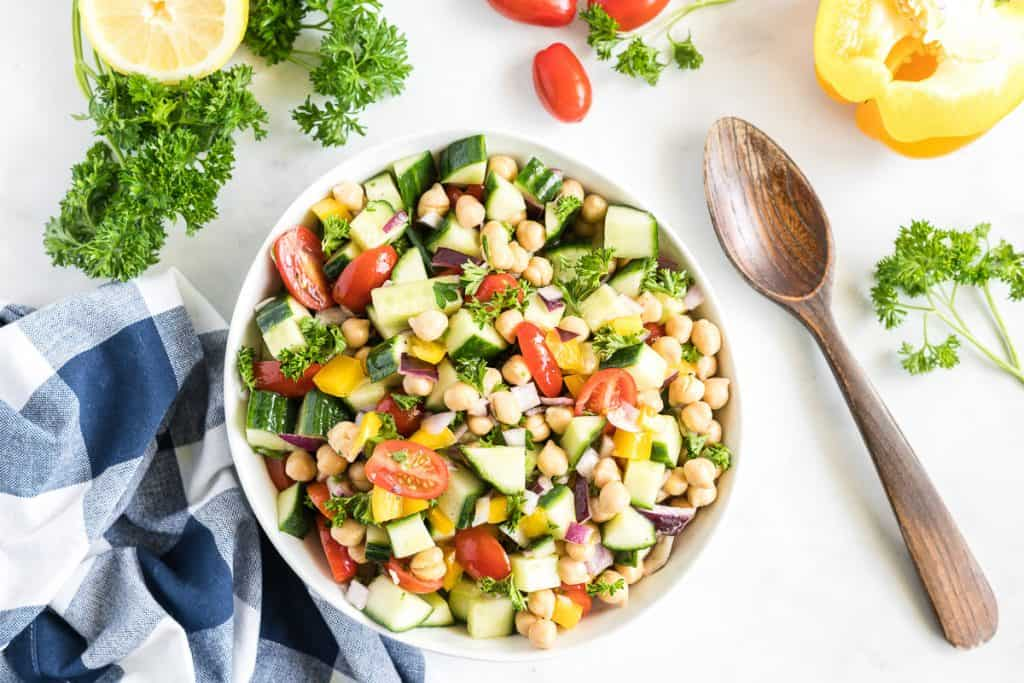A white bowl of Chickpea Salad with a wooden spoon and ingredients scattered around it.