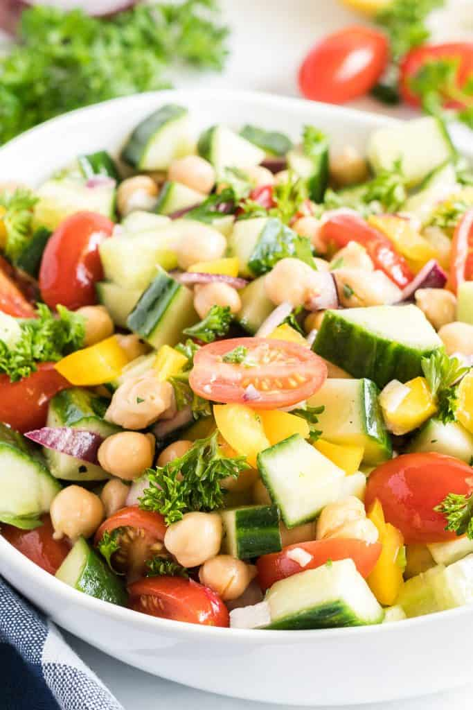 A close up of the salad with chickpeas, cucumbers, and tomatoes in a white serving bowl.