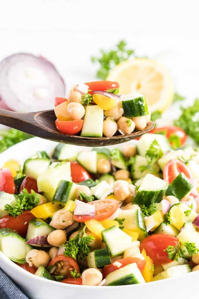 A wooden spoon scoops up some of the Chickpea Salad.