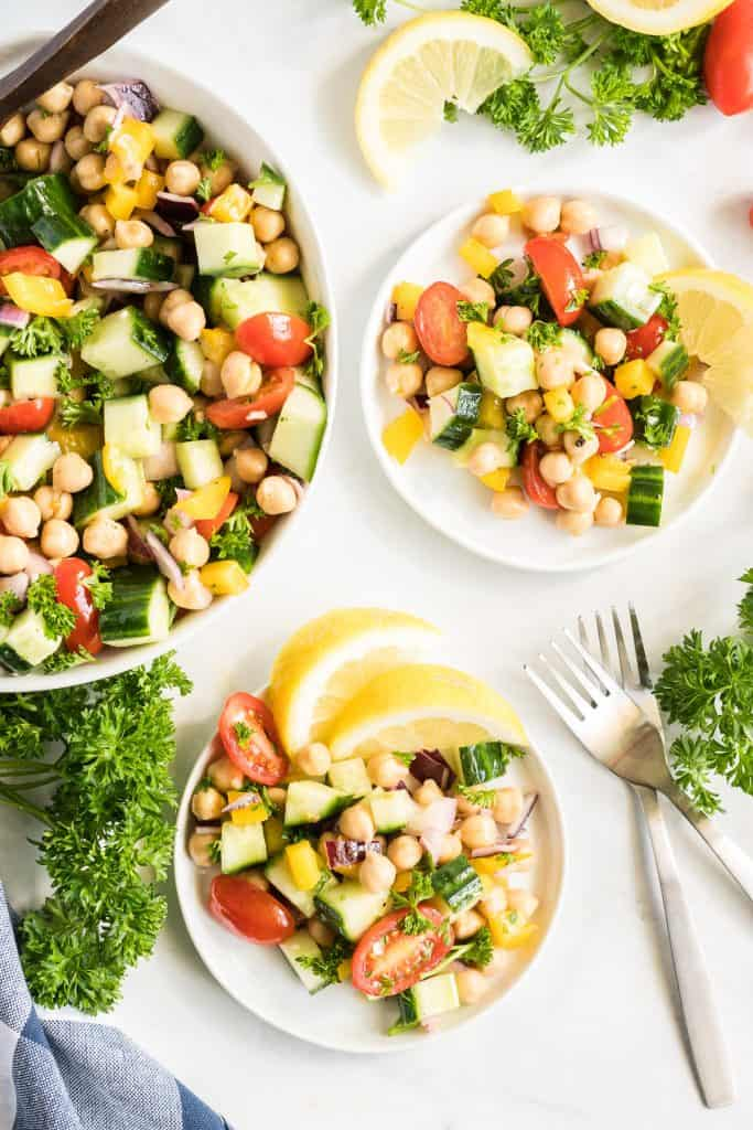 Two small white plates with a serving of Chickpea Salad and lemon slices.