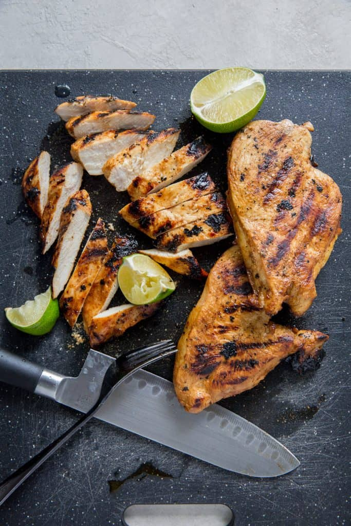 Pieces of sliced grilled chicken on a black cutting board with a knife.