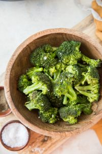 Steamed broccoli in a wood bowl with an orange napkin and salt to the side