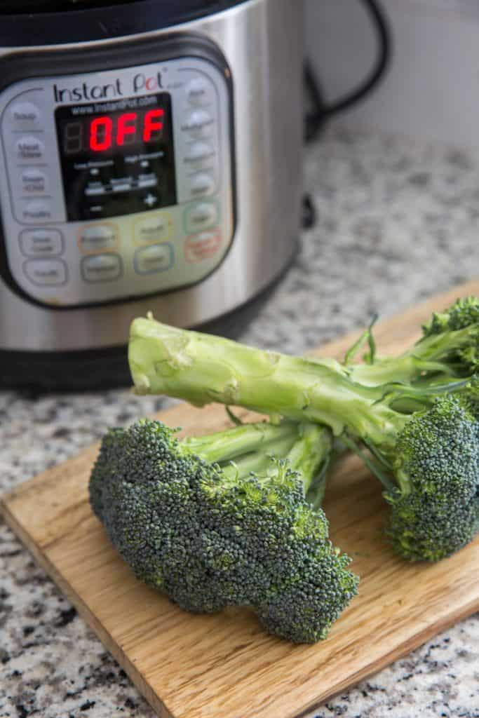 2 heads of broccoli on a cutting board with an Instant Pot in the background