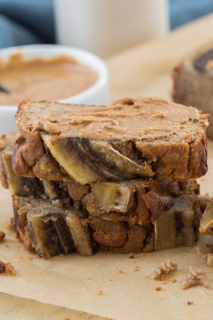 closeup image of sliced banana bread topped with almond butter