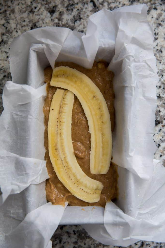 banana bread batter in a pan lined with parchment topped with a sliced banana