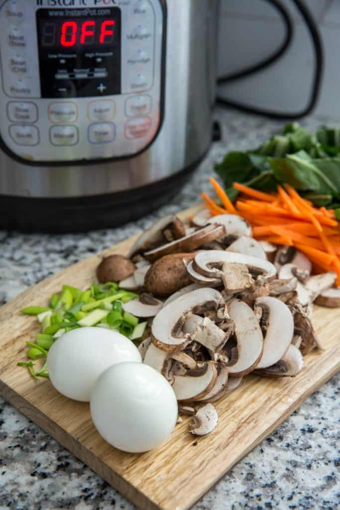 sliced vegetables on a cutting board with an instant pot in the background