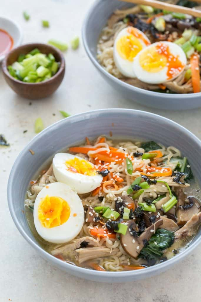 close up image of low sodium instant pot ramen with sliced green onions in a small bowl