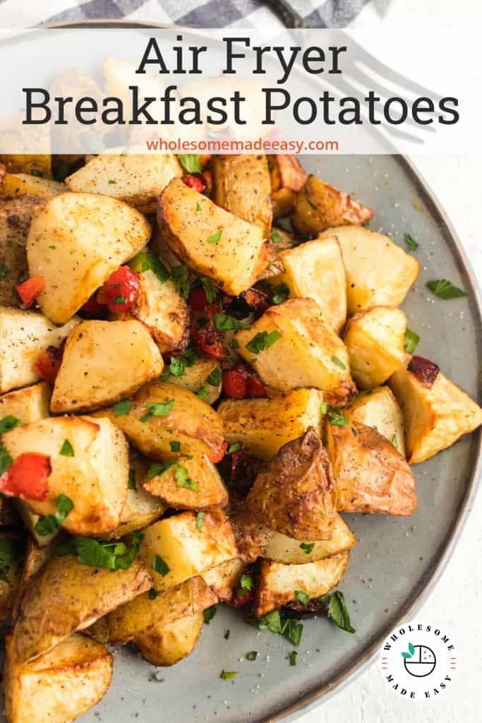 Chunks of air fried potatoes with red bell pepper on a plate.