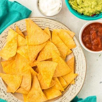air fryer tortilla chips on a plate with salsa , guacamole and sour cream on the side in bowls.
