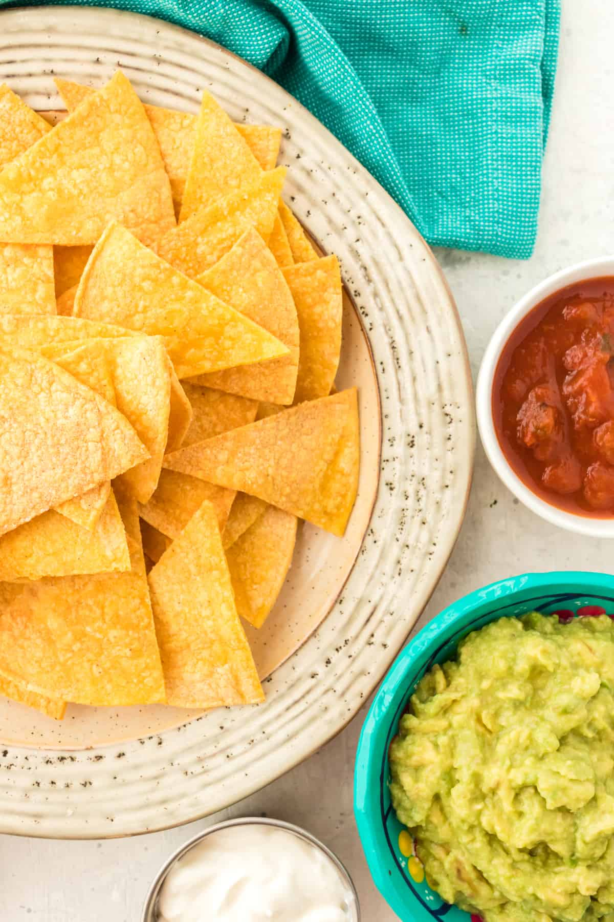 Close up of air fryer tortilla chips on a plate with guacamole, salsa and sour cream on the side in bowls.