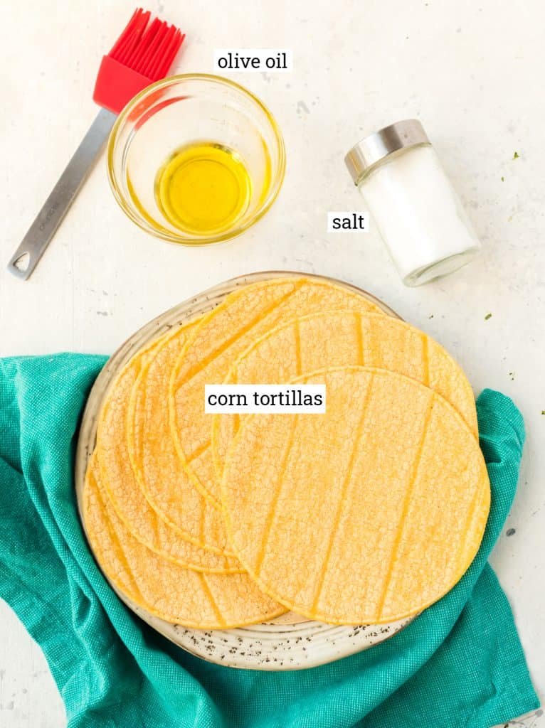 Olive oil, salt and corn tortillas on a table.