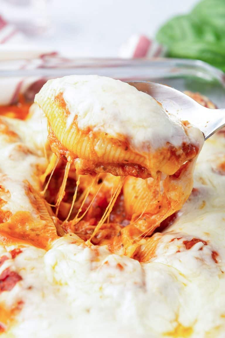 A spoon lifts a cheesy stuffed pasta shell from a dish.