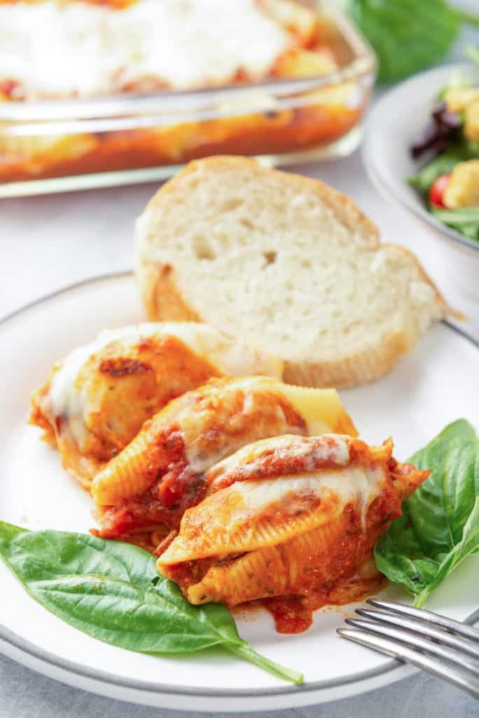 Three stuffed pasta shells topped with marinara and cheese on a white plate.