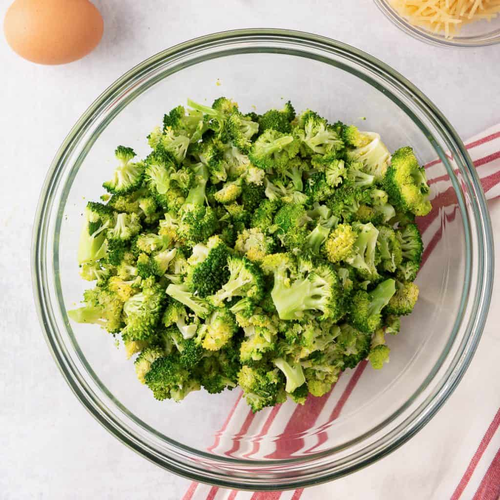 Partially cooked chopped broccoli in a glass bowl.