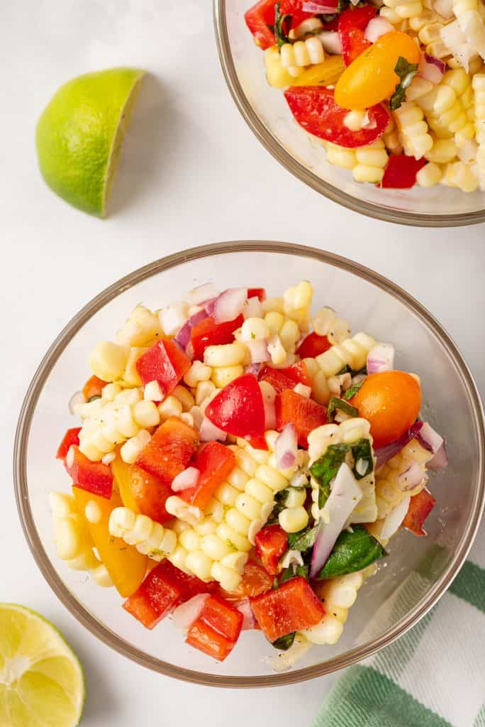 A glass bowl filled with corn and tomato salad