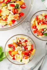 Two small bowls filled with corn salad with a larger bowl in the background.