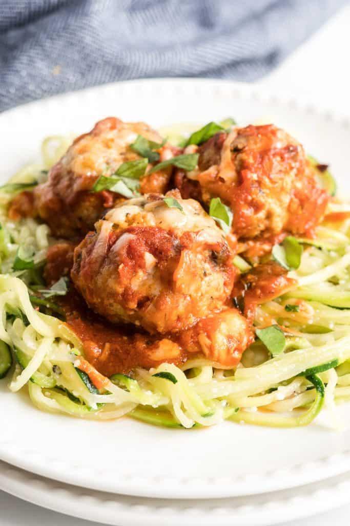 A closeup of three turkey meatballs on zucchini noodles.