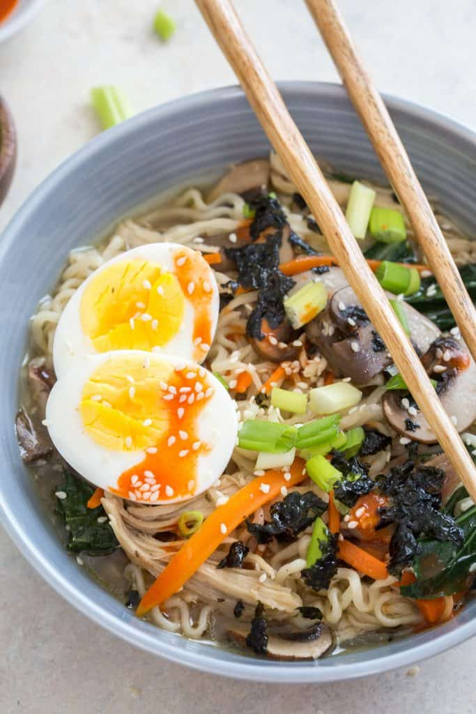 Ramen in a bowl with a soft boiled egg and chopsticks.