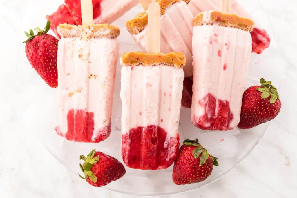 plate of strawberry cheesecake popsicles