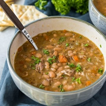 A white bowl filled with navy bean soup.