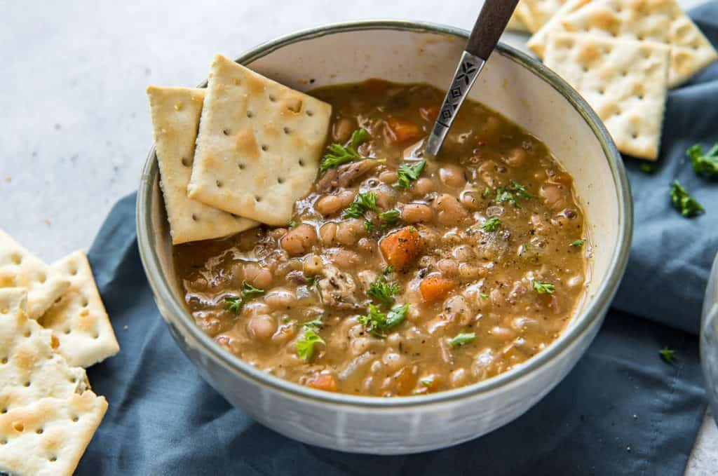 A bowl of navy bean soup with a spoon and crackers.