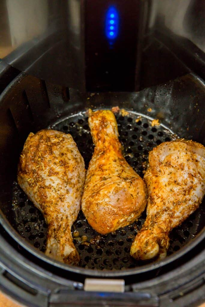 raw chicken drumsticks seasoned and in an air fryer
