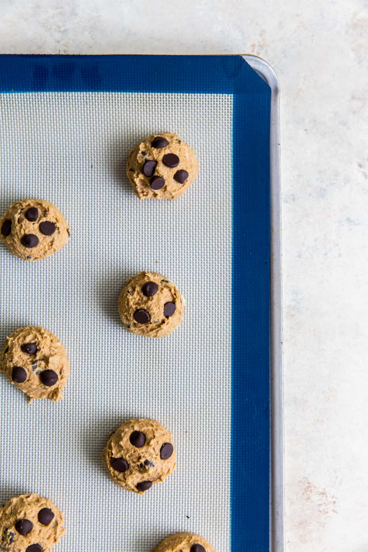 chocolate chip cookie dough rolled into balls on a silicone baking mat