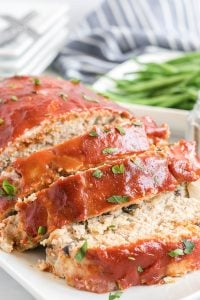 A sliced turkey meatloaf on a white platter.