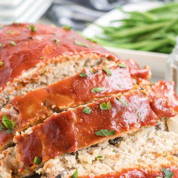 A sliced turkey meatloaf on a white platter.
