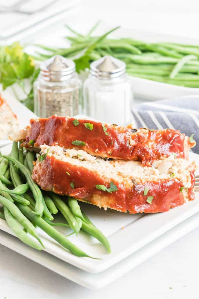 Two slices of meatloaf on a plate with green beans.