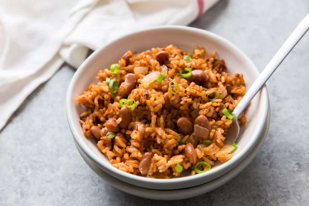 low sodium rice and beans in a white bowl with a spoon and napkin