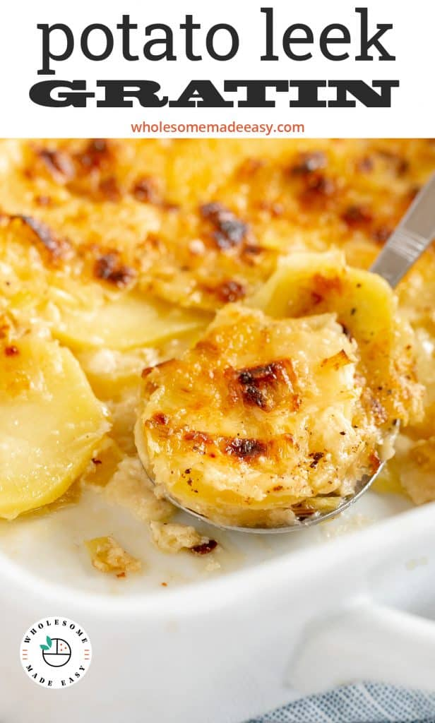 A spoon scoops up some Potato Leek Gratin from a baking dish.
