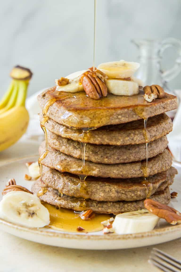 Maple syrup pouring over a stack of Banana Oat Pancakes.