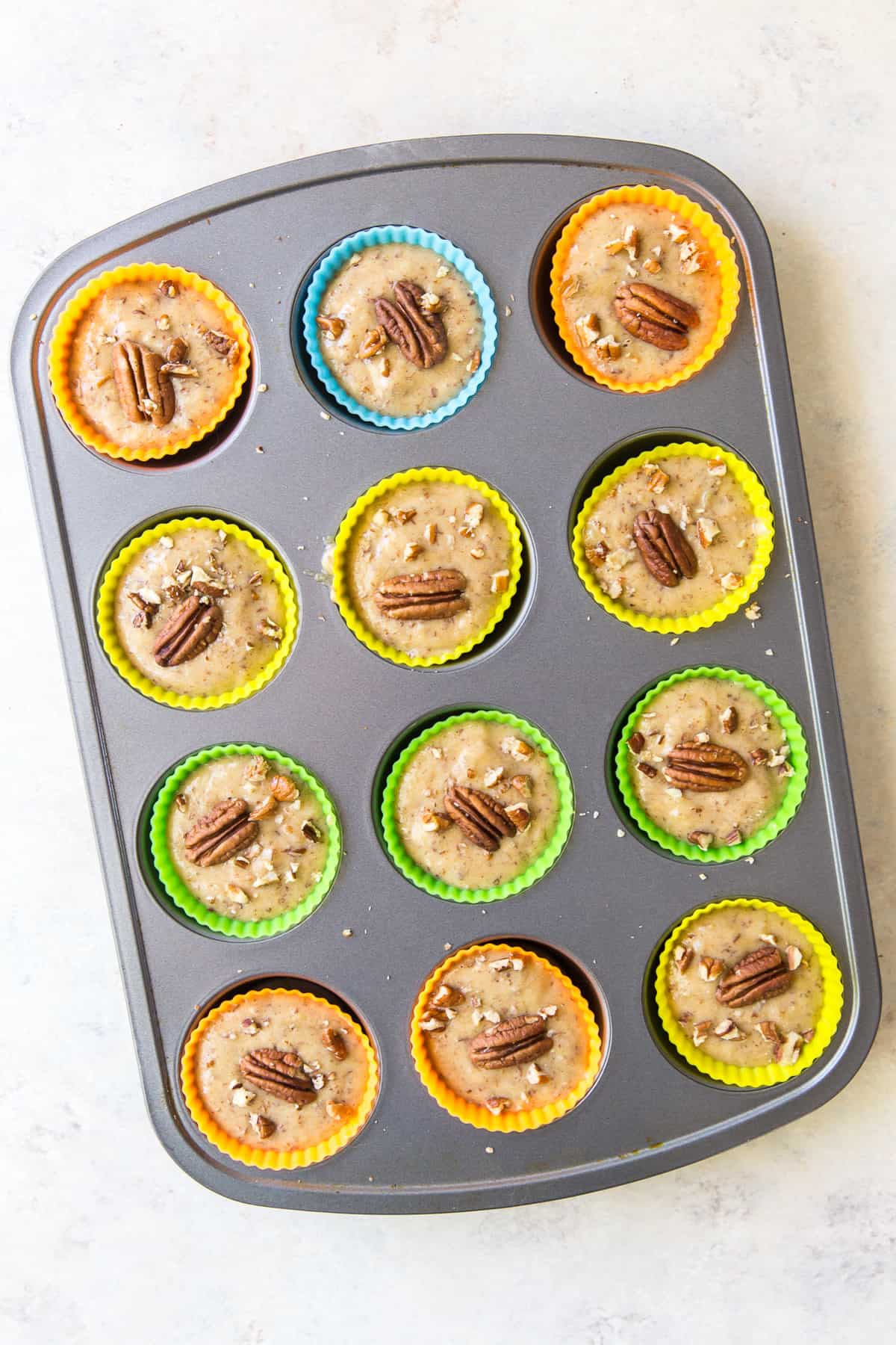 Muffin batter in colorful silicone baking cups in a muffin pan.