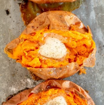 Three baked sweet potatoes topped with butter shot from over the top.