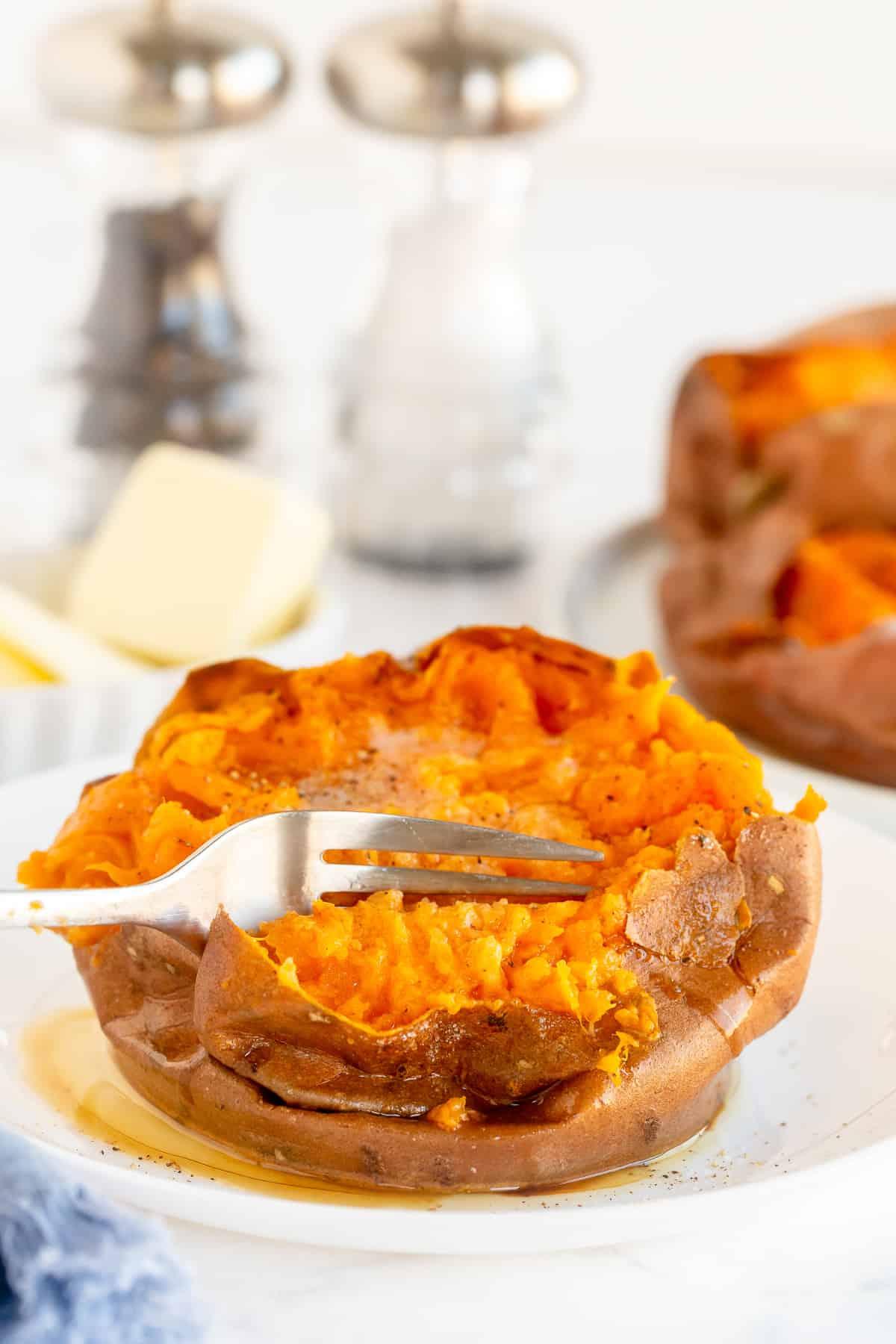 A fork breaks into a baked sweet potato.
