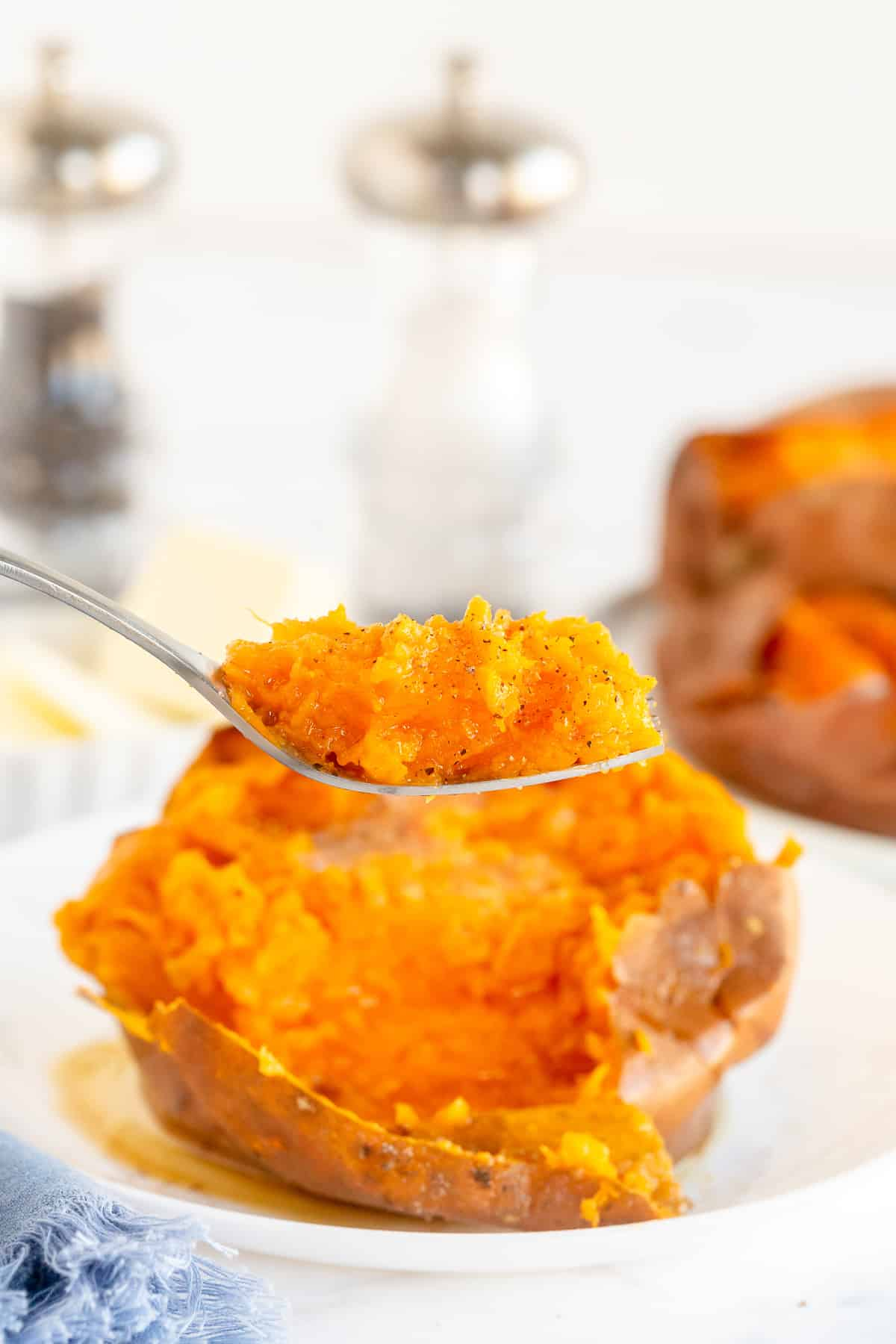 A fork lifts a bite of sweet potato.
