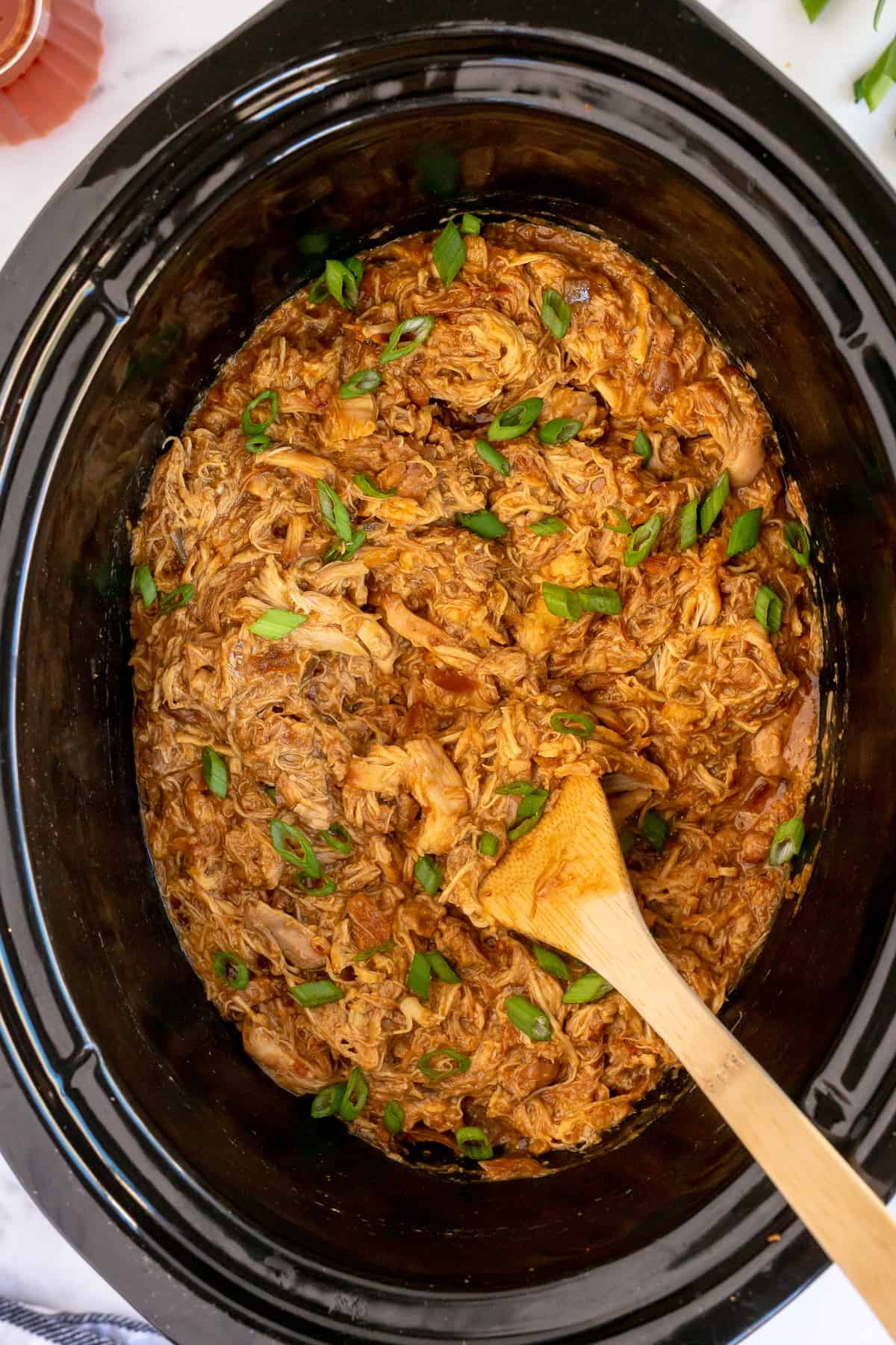 A wooden spoon stirs Honey Soy Chicken in a slow cooker.