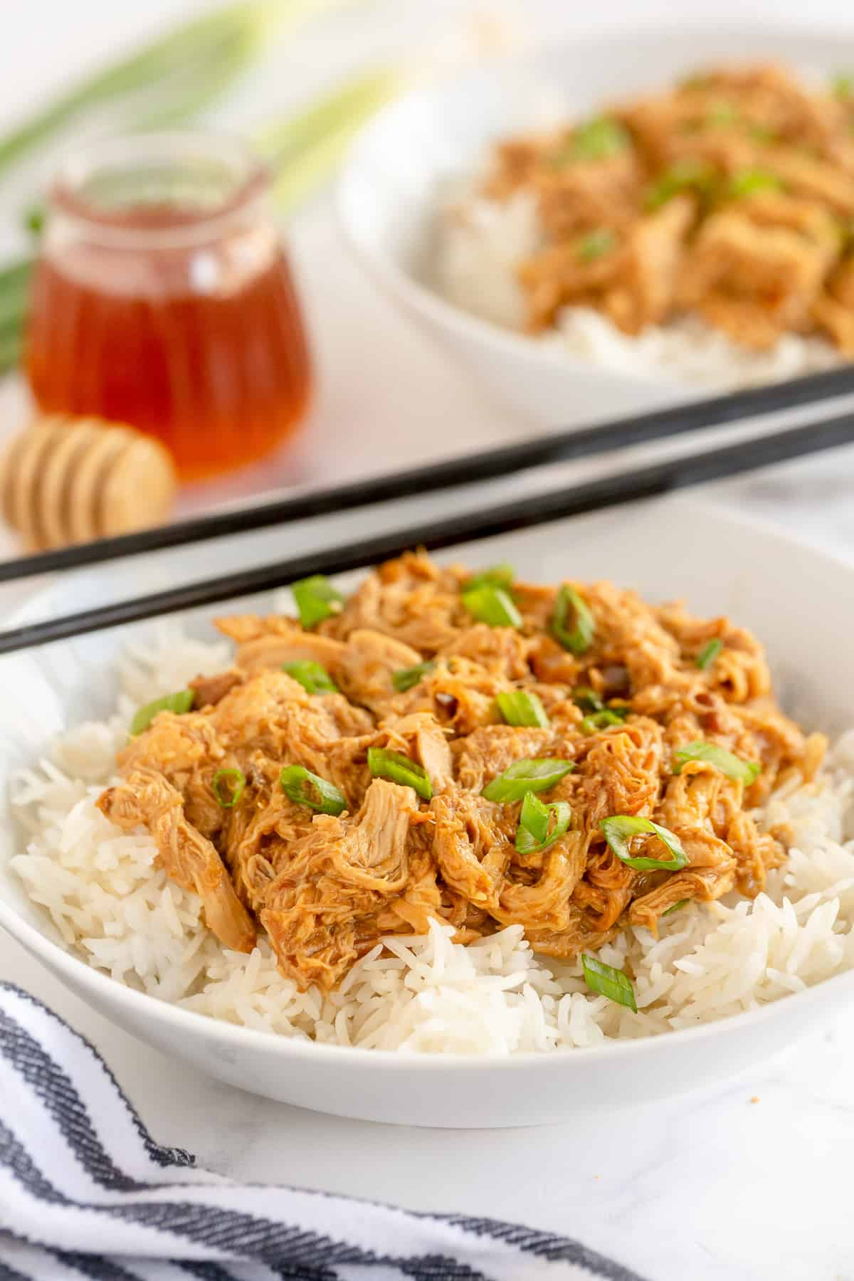 A bowl of rice topped with Honey Soy Chicken and chopsticks.