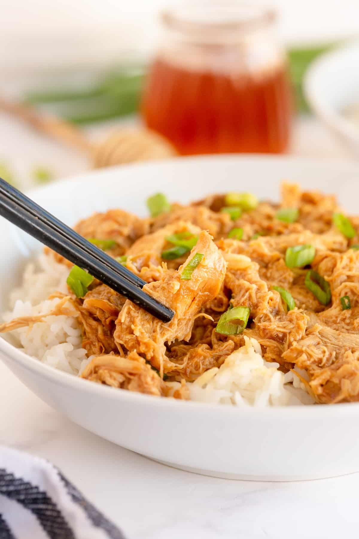 Chopsticks lift a piece of chicken from a bowl.