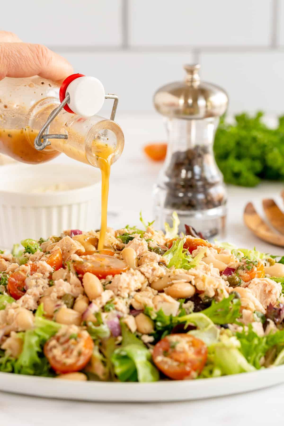 Vinaigrette is poured over a salad.