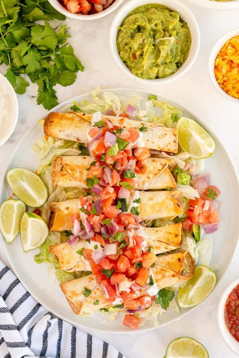 A platter of taquitos topped with pico de gallo shot from over the top.